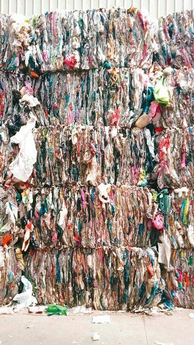 中部某回收業者回收的塑膠袋無處去,只能壓縮暫存在回收站內,不知如何處理。 圖/李...