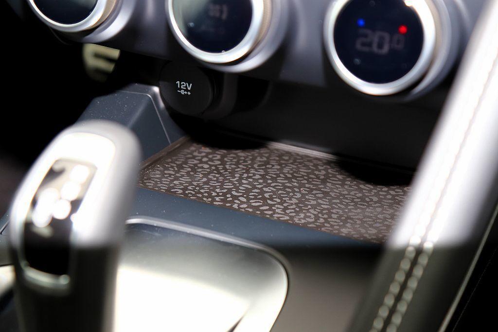 Jaguar有著許多設計小巧思,例如空調控制旋鈕下放的置物空間採用豹紋設計,但沒有加入無線充電功能就稍嫌可惜。 記者張振群/攝影