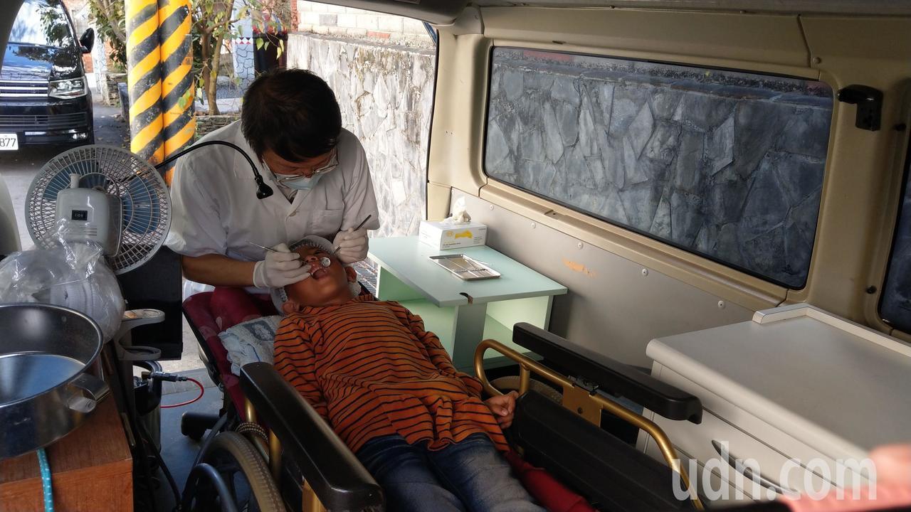牙醫王佑崑(左)以廂型車充當巡迴車,輪椅搬進車內當診療椅,不鏽鋼桶加漏斗充當漱口...