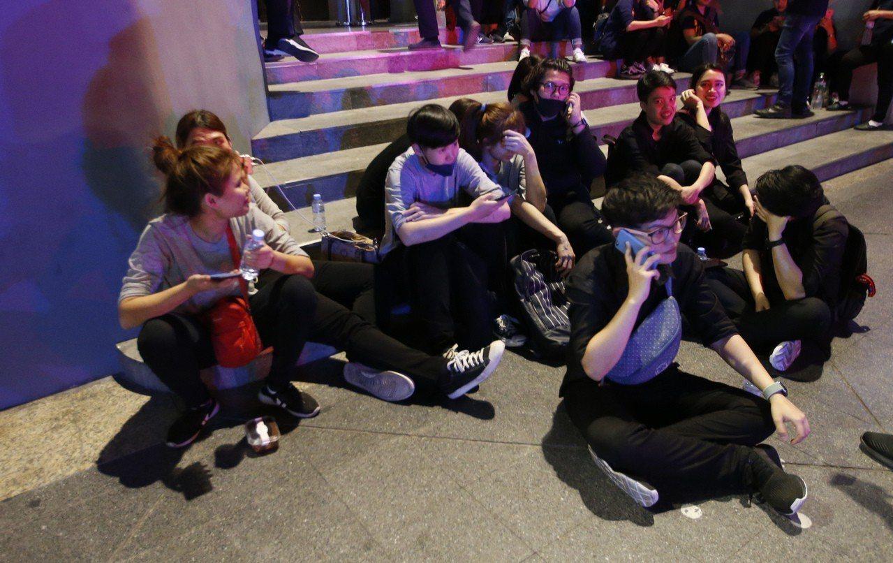 百貨公司員工被疏散到外面席地而坐。(美聯社)
