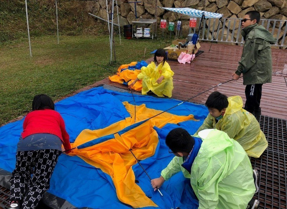 學生團結合作在雨中搭帳篷。圖/趙廷軒提供