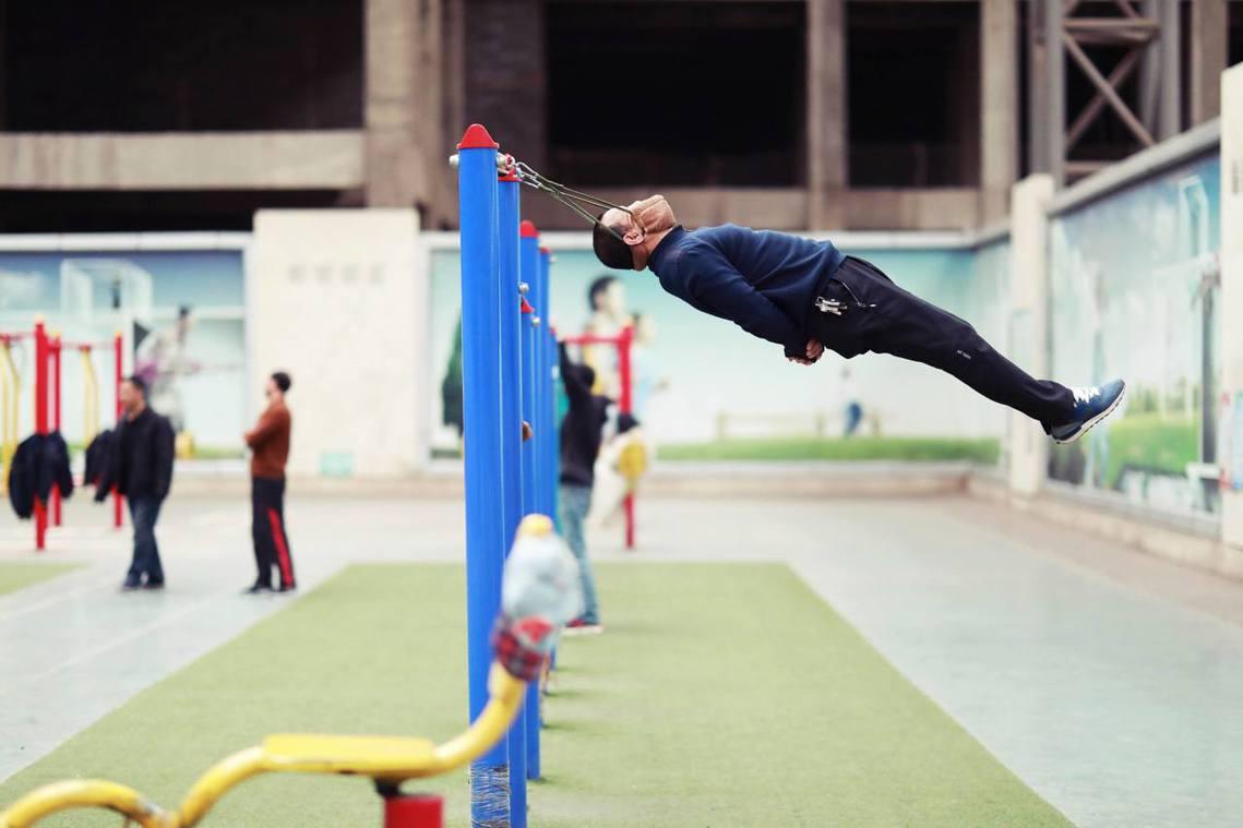 在中國瀋陽的一處健身運動場,民眾強身健體的「頸椎牽引之術」,利用自製的吊頸裝置進...