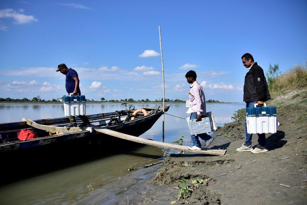 印度11日起舉辦下議院選舉,北部阿薩姆省選務人員10日乘船運送電子投票機。路透
