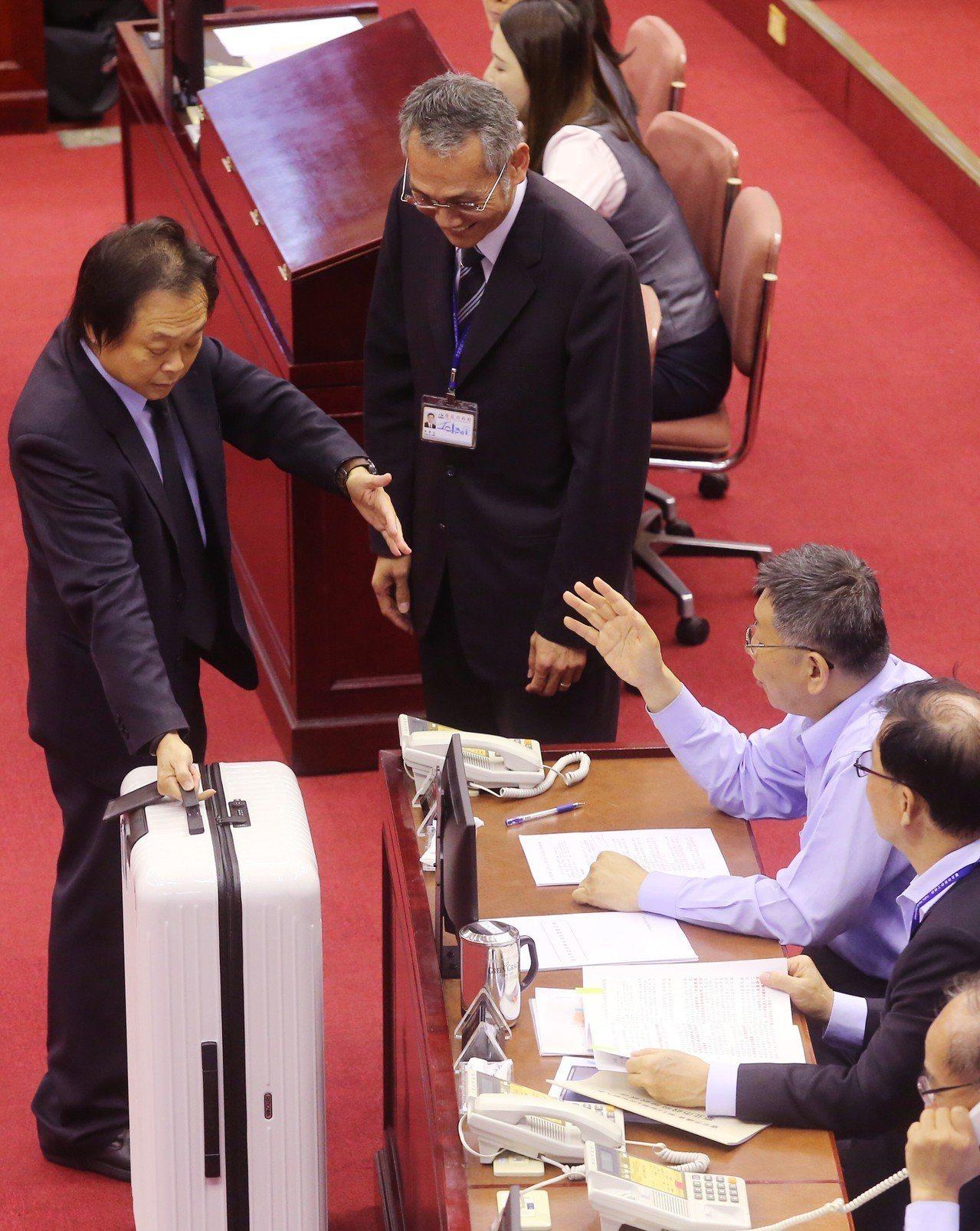 台北市議員王世堅(左)昨天痛批市長柯文哲既然無心市政就早一點打包走人,當場推出行...