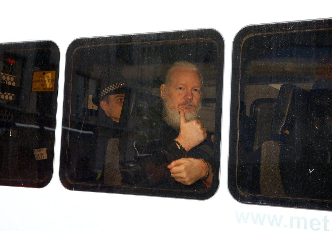 亞桑傑坐上警車,跟窗外比大拇指。路透