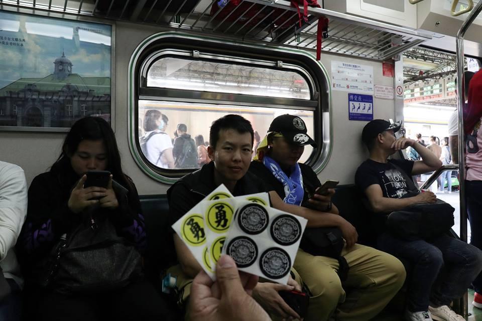 房婧如在臉書貼第一天在火車上遇到醫療團隊年輕人,送他們印有「勇」字的貼紙照片,這...