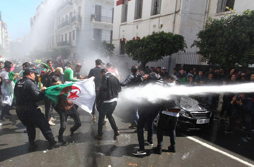 阿爾及利亞示威者9日在首都阿爾及爾要求臨時總統班沙勒下台,當局以水柱驅趕。(法新...