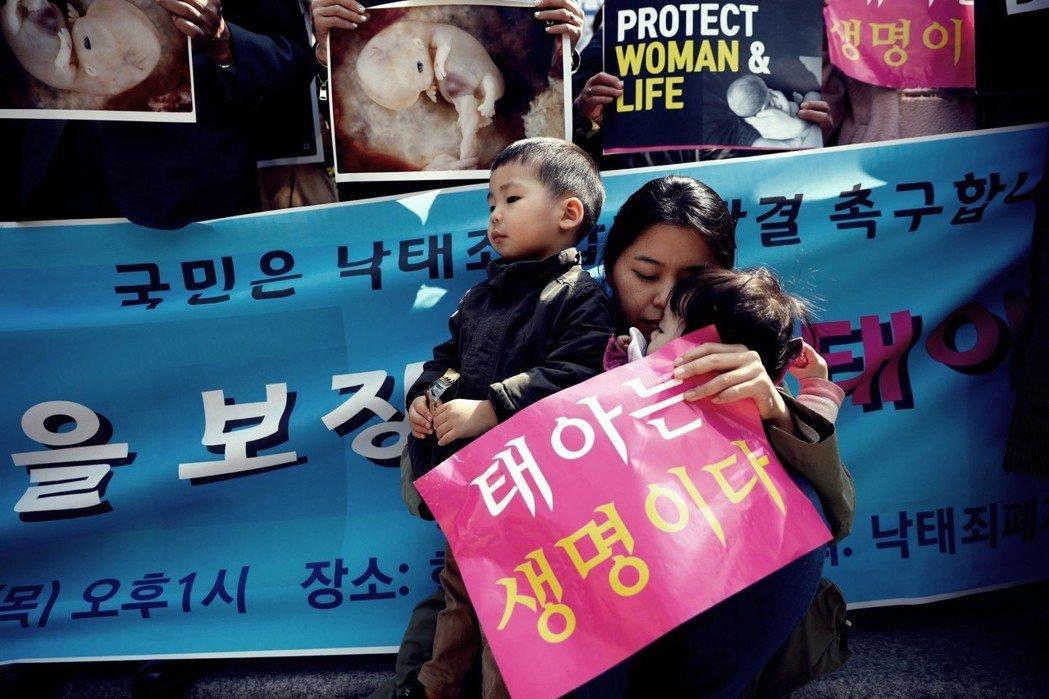 主張保留墮胎罪的反墮胎派,多位母親著帶著2、3歲的嬰孩,或者也有人拿著母體內胎兒...