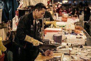 用專注的神情和熟練的刀法分切鮮魚,是魚市場的日常風景 (攝影/汪正翔)