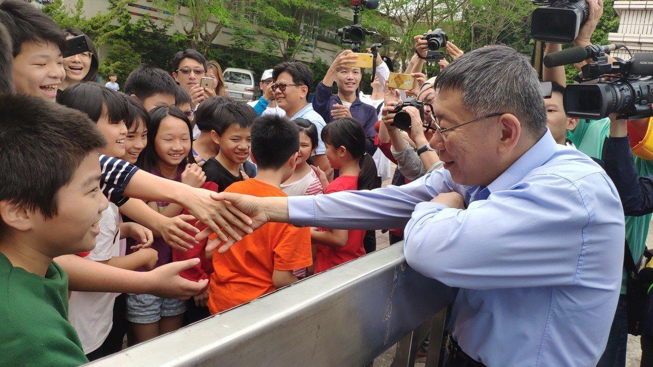 台北市長柯文哲(右)聽見學童呼喊,便走過馬路與小朋友互動。記者李京昇/攝影