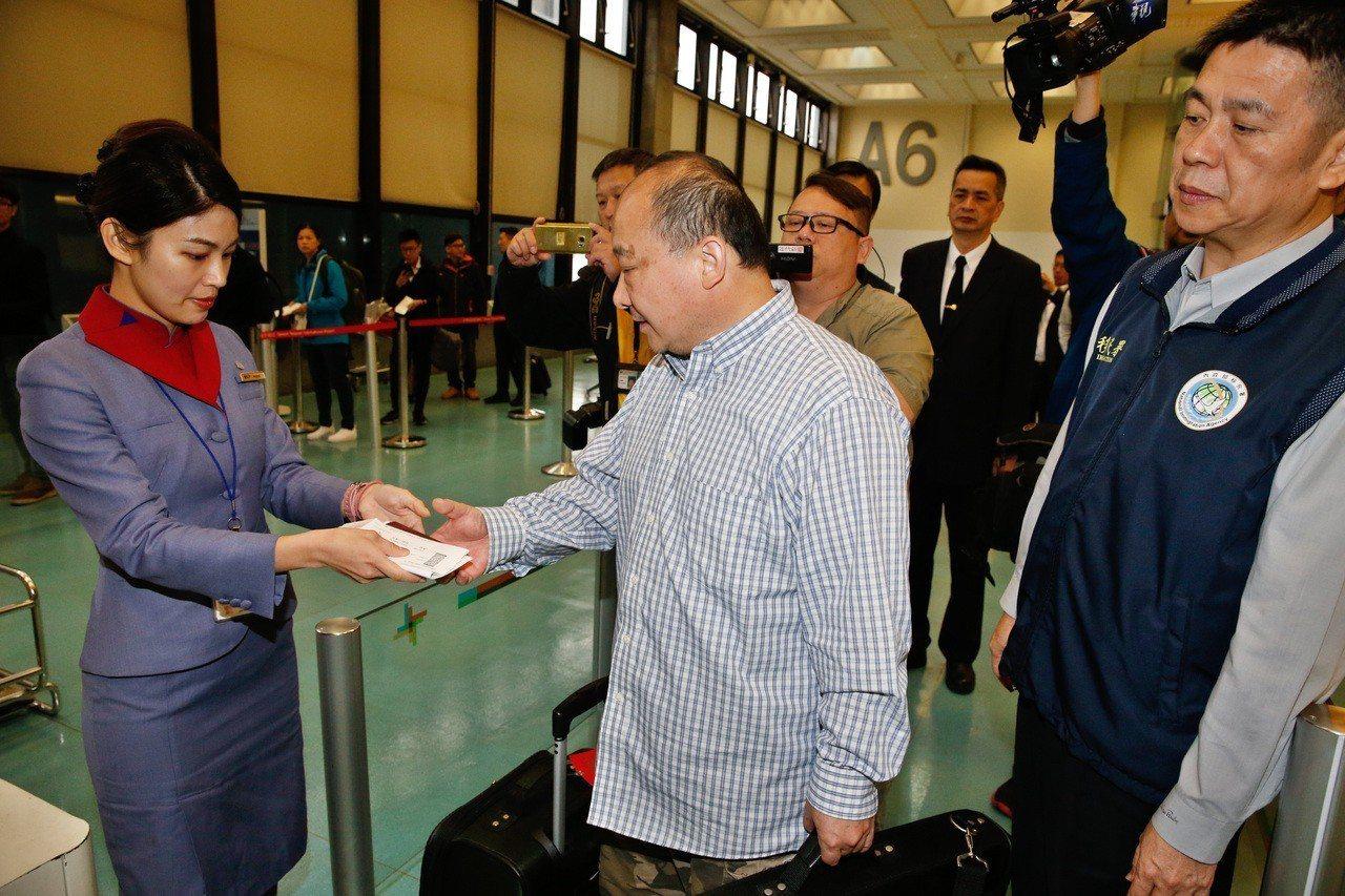 旅美大陸地區的武統學者李毅(中)遭移民署強制出境,在多名移民署人員戒護下前往登機...