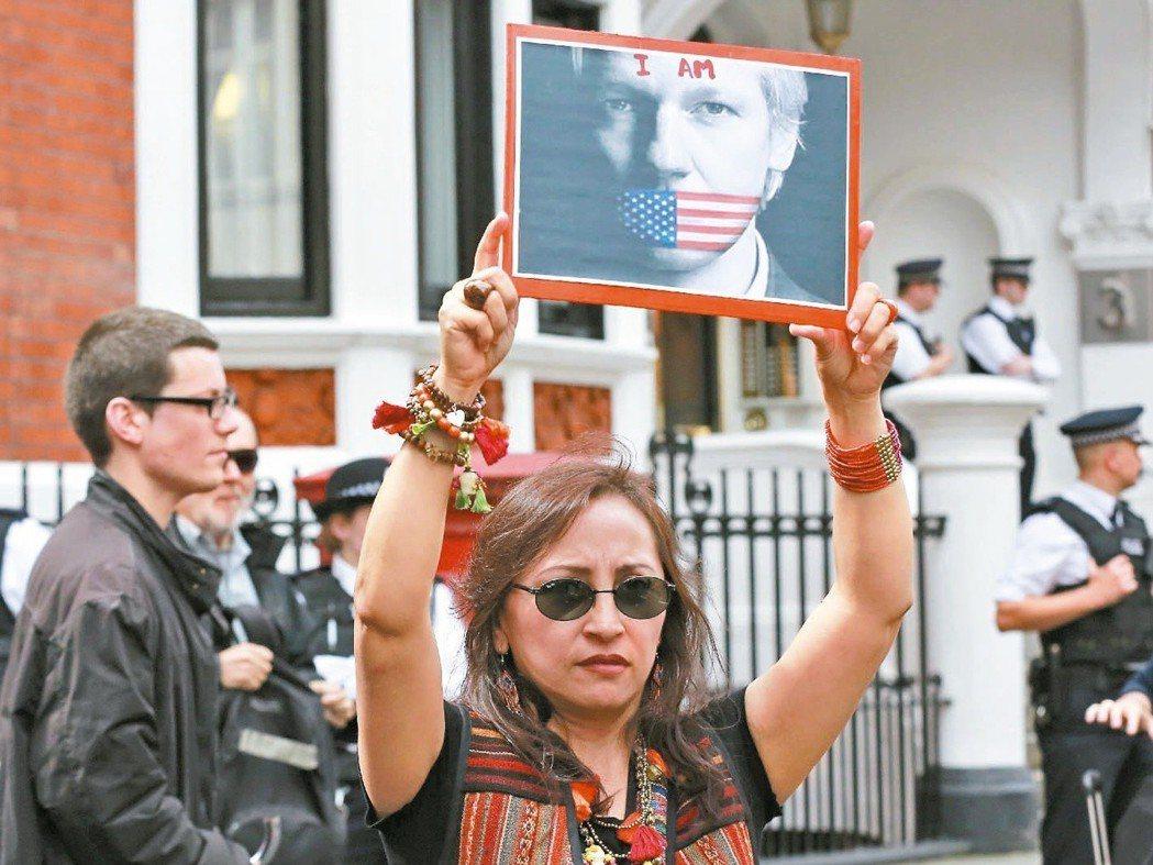 2012年一名抗議者在厄瓜多駐倫敦大使館外,高舉以亞桑傑照片為主的標語牌,表達對...