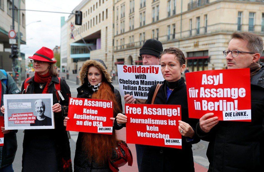 德國民眾十二日在英國駐德國大使館前抗議亞桑傑遭逮捕,其中一個標語寫著「新聞報導不...
