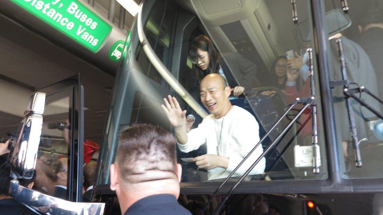 韓國瑜在群眾簇擁下步出機場,隨後進入接送他的遊覽車,韓見到僑胞仍圍著車旁不散去,...