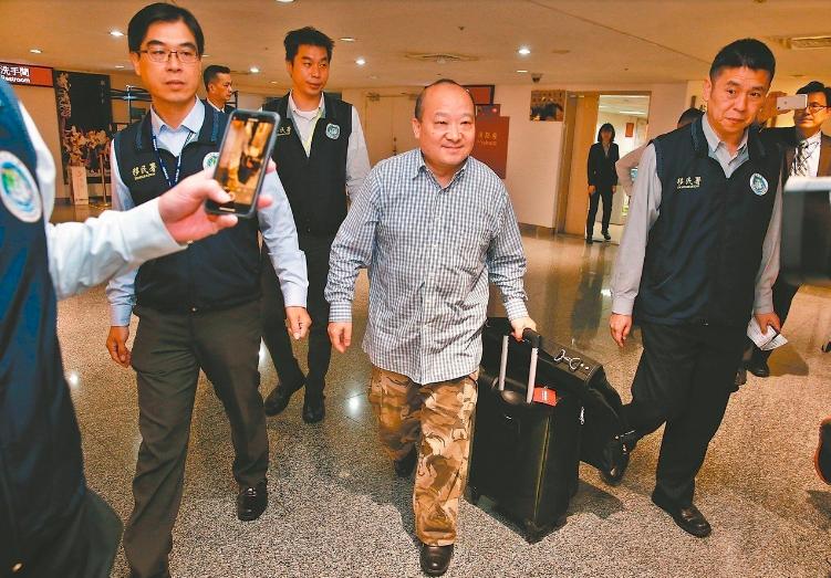 旅美的大陸學者李毅(中)遭移民署強制出境,在多名移民署人員戒護下前往辦理出境手續...