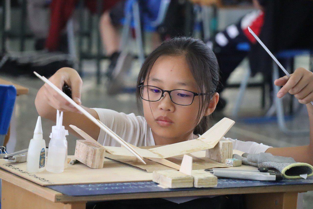 高雄市國中生手擲機飛行競賽今天舉行,選手小心翼翼製作組裝完整飛行器的機身、機翼、...