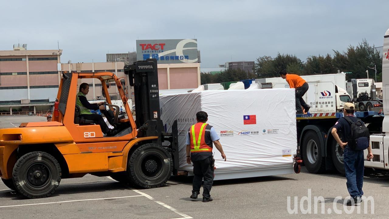福衛7號衛星本體,14日中午運抵桃園機場華儲公司,由多名裝卸人員指揮,小心翼翼卸...
