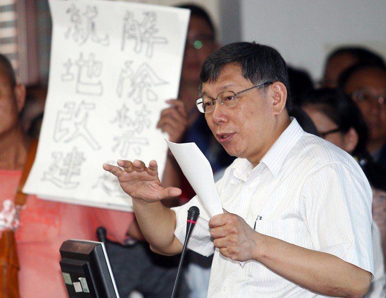 2018年6月,台北市長柯文哲親自出席都委會的社子島開發審查會議,現場有居民高舉「解除禁建、就地改建」的標語。 圖/聯合報系資料照