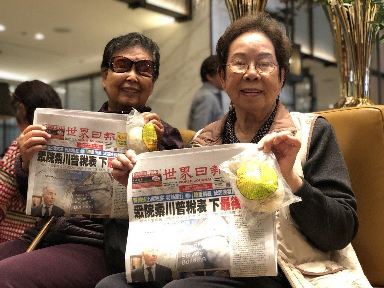民眾拿著主辦單位在演講會後發送的包子與世界日報,意為「支持土包子選總統」。記者王...