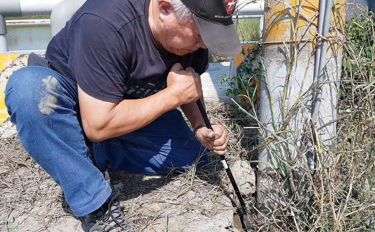 台灣動物緊急救援小組大隊長倪兆成拿著挖掘工具,鑿開水泥石塊進行救援。圖/台灣動物...