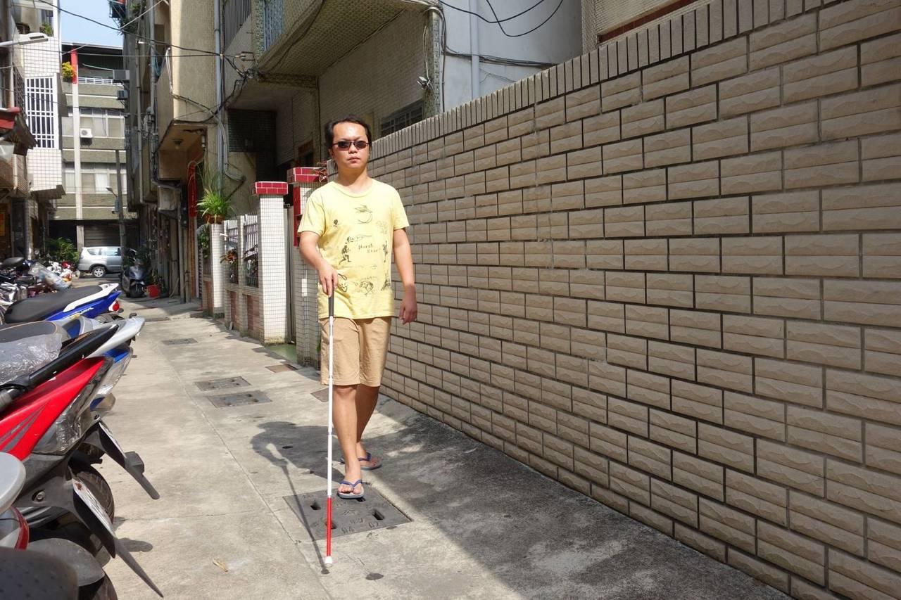 居住在巷弄內的許家峰,憑藉手杖,辨識周遭有無障礙物,獨立外出搭車工作。圖/ 慈...