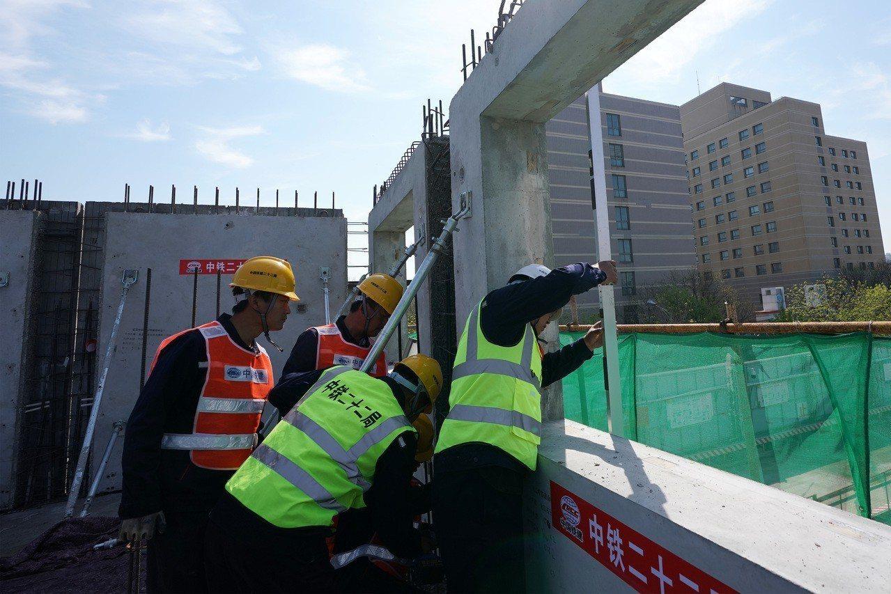 新華社狠批超長工時的「996工作制」。圖為北京烈日下的施工人員在進行建物外牆板模...