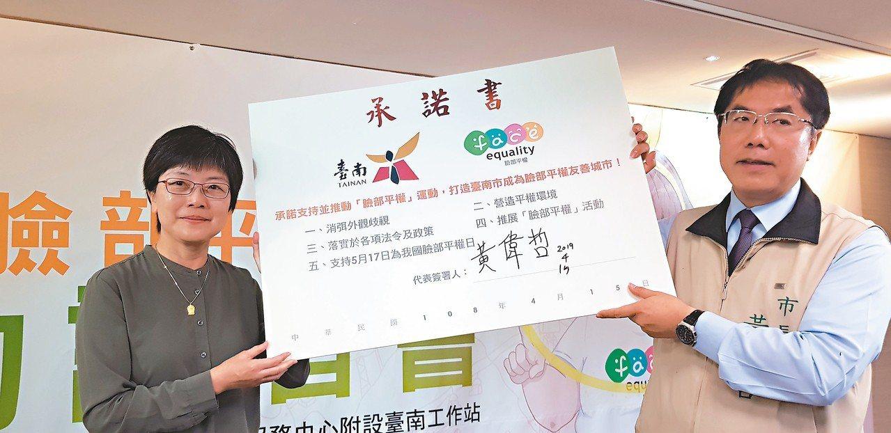 台南市長黃偉哲(右)昨天簽署承諾書推動臉部平權,左為陽光基金會執行長舒靜嫻。 記...