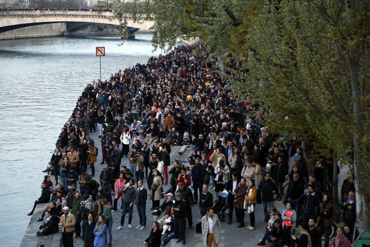 火燒法國巴黎聖母院,民眾在塞納河畔看著不遠處的聖母院。美聯社