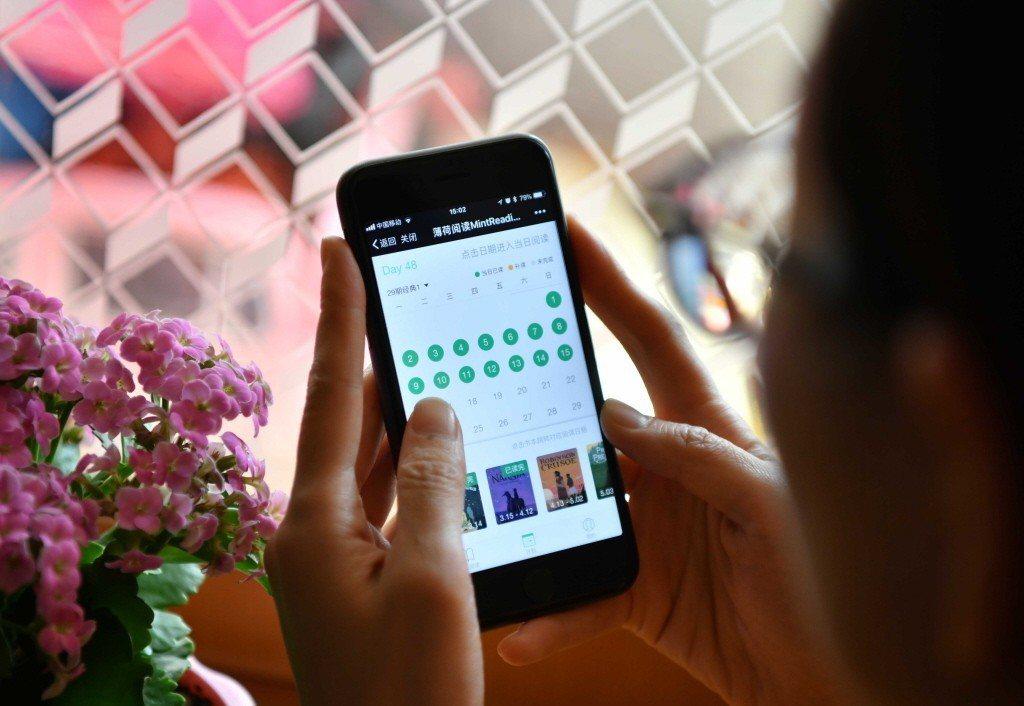 一名北京市民在家中通過手機在一個微信公眾號上閱讀「打卡」。 圖/新華社