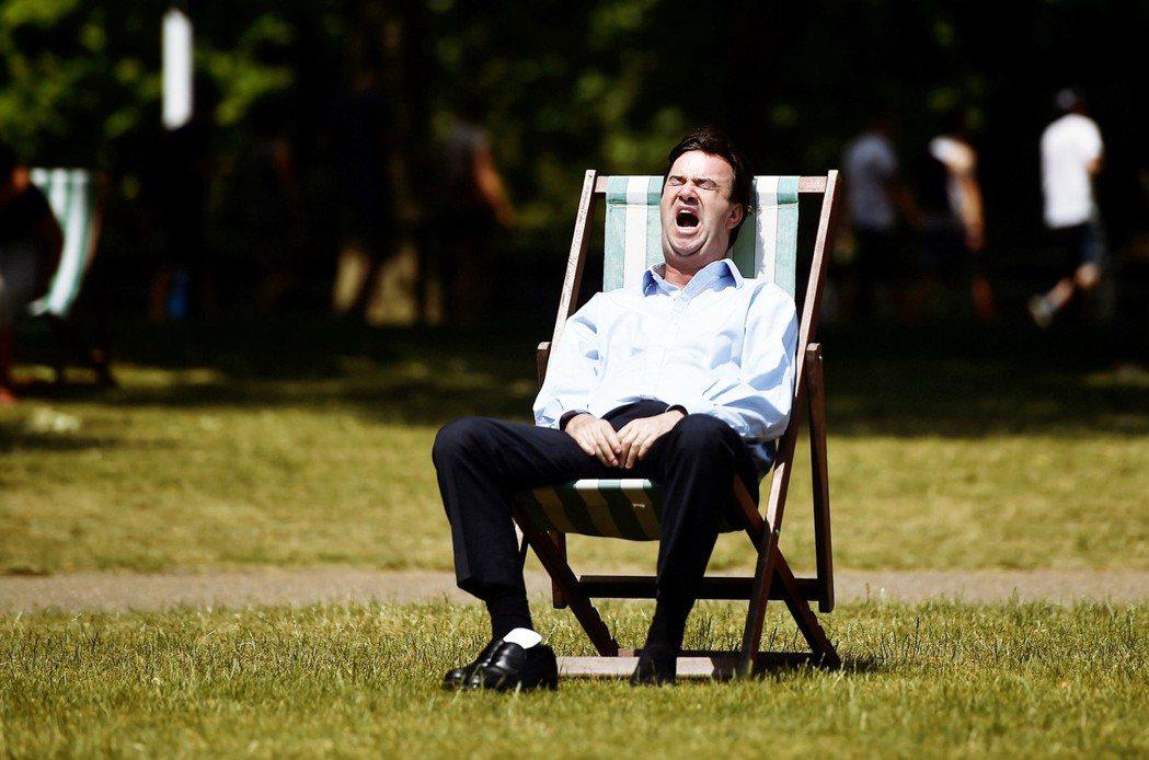 「什麼都是假的,放假才是真的!」圖為倫敦聖詹姆斯公園曬太陽的疲憊上班族。 圖/路...
