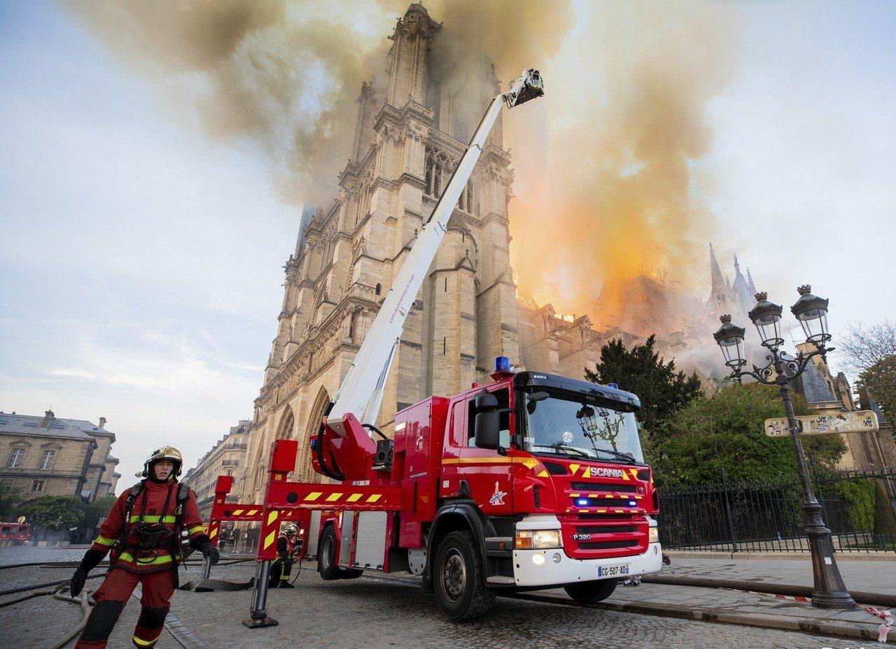 法國巴黎消防員不眠不休搶救聖母院。(美聯社)