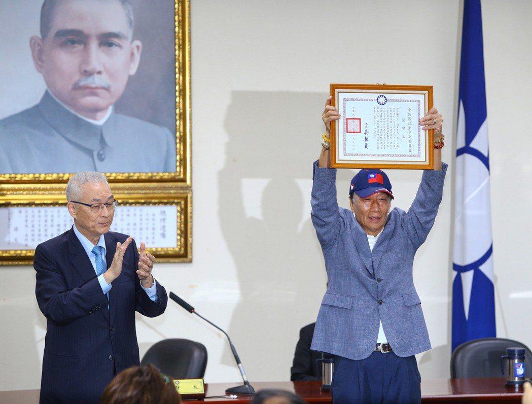 有五十年國民黨黨齡的鴻海董事長郭台銘(右)昨天從黨主席吳敦義(左)手上接下榮譽狀...