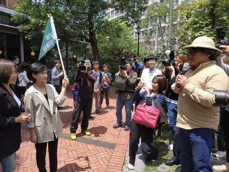 文化部長鄭麗君(舉旗者)帶著群眾漫步在台灣博物館園區,聆聽主持人講解樟腦工廠的歷...