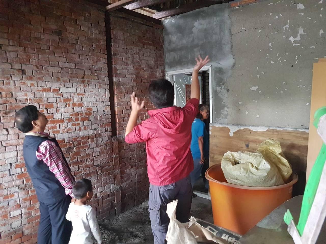 張銘烈(左)牽著陳姓孫子的手進屋勘查屋頂受損情形。記者尤聰光/翻攝
