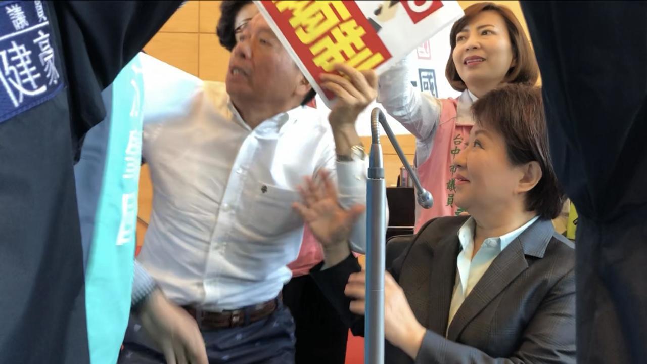台中市長盧秀燕(右)被民進黨議員們包圍,要求說明「市府是否被抹紅?」藍營議員相護...
