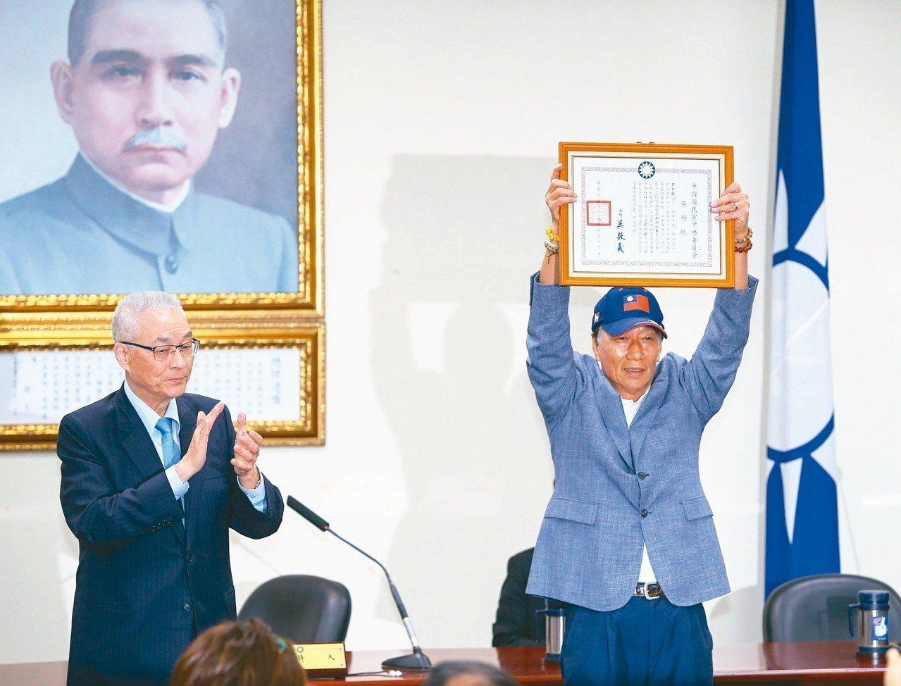 有五十年國民黨黨齡的鴻海董事長郭台銘(右)昨從黨主席吳敦義(左)手上接下榮譽狀,...