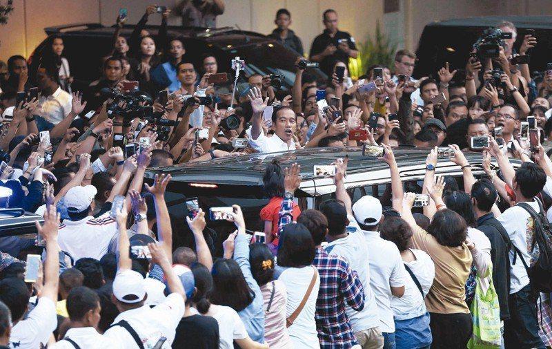 印尼總統佐科威(中)十七日針對大選計票結果發表談話後,向大批支持者揮手致意。 (美聯社)
