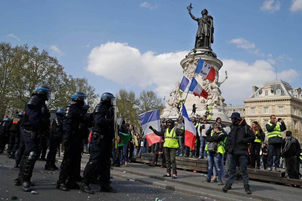 示威民眾13日穿著黃背心在巴黎街頭抗議,這是黃背心運動連續第22個周末舉行。(法...