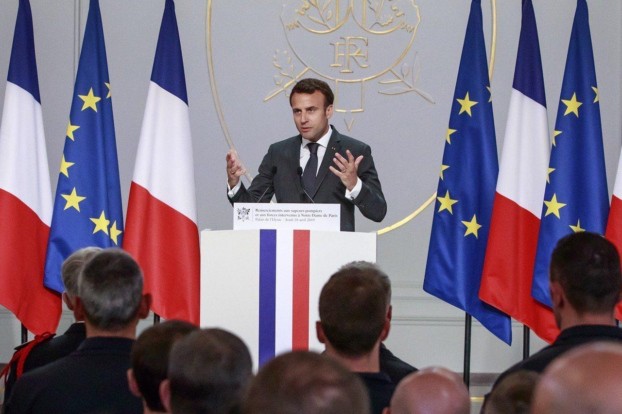 法國總統馬克宏18日在艾里榭宮表揚聖母院救火有功的消防員。(美聯社)
