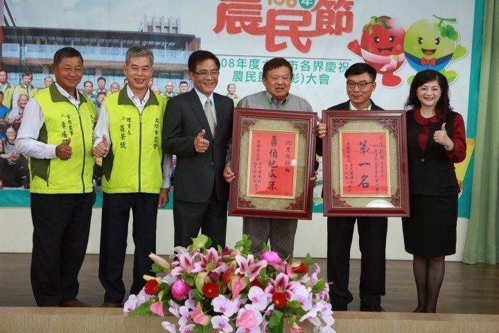 太保市農會總幹事黃麗貞(右起),表揚農民張耿赫善用農業科學數據,以自行研發「離地...