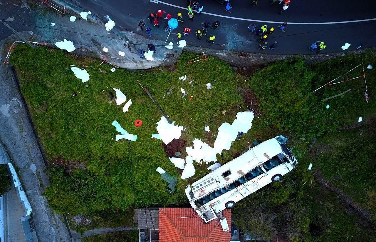 空拍影像可見,失控衝出道路的遊覽車似乎撞上下坡處的一間民宅。法新社