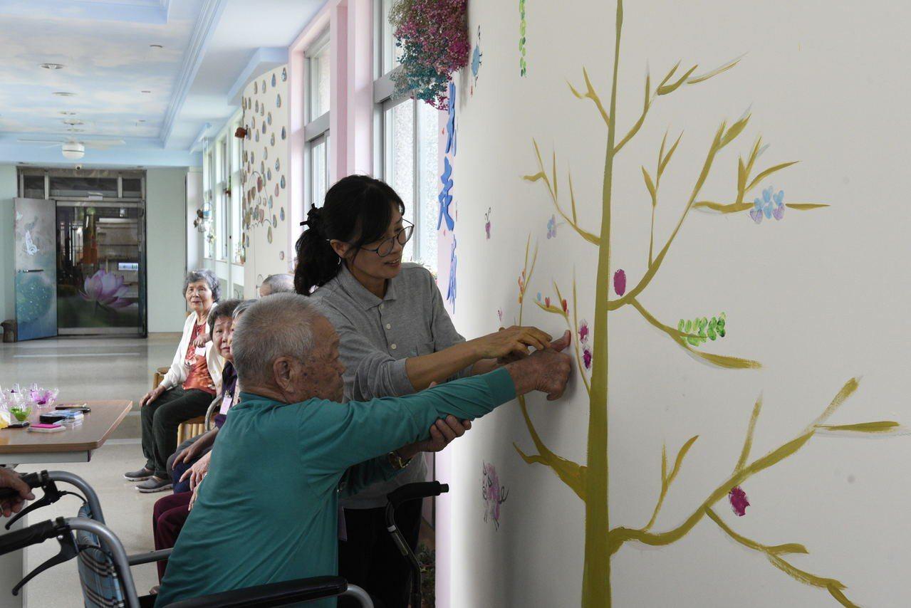 志工褚秋華(右)帶著老人家用拇指在牆上作畫。圖/大林慈濟醫院提供