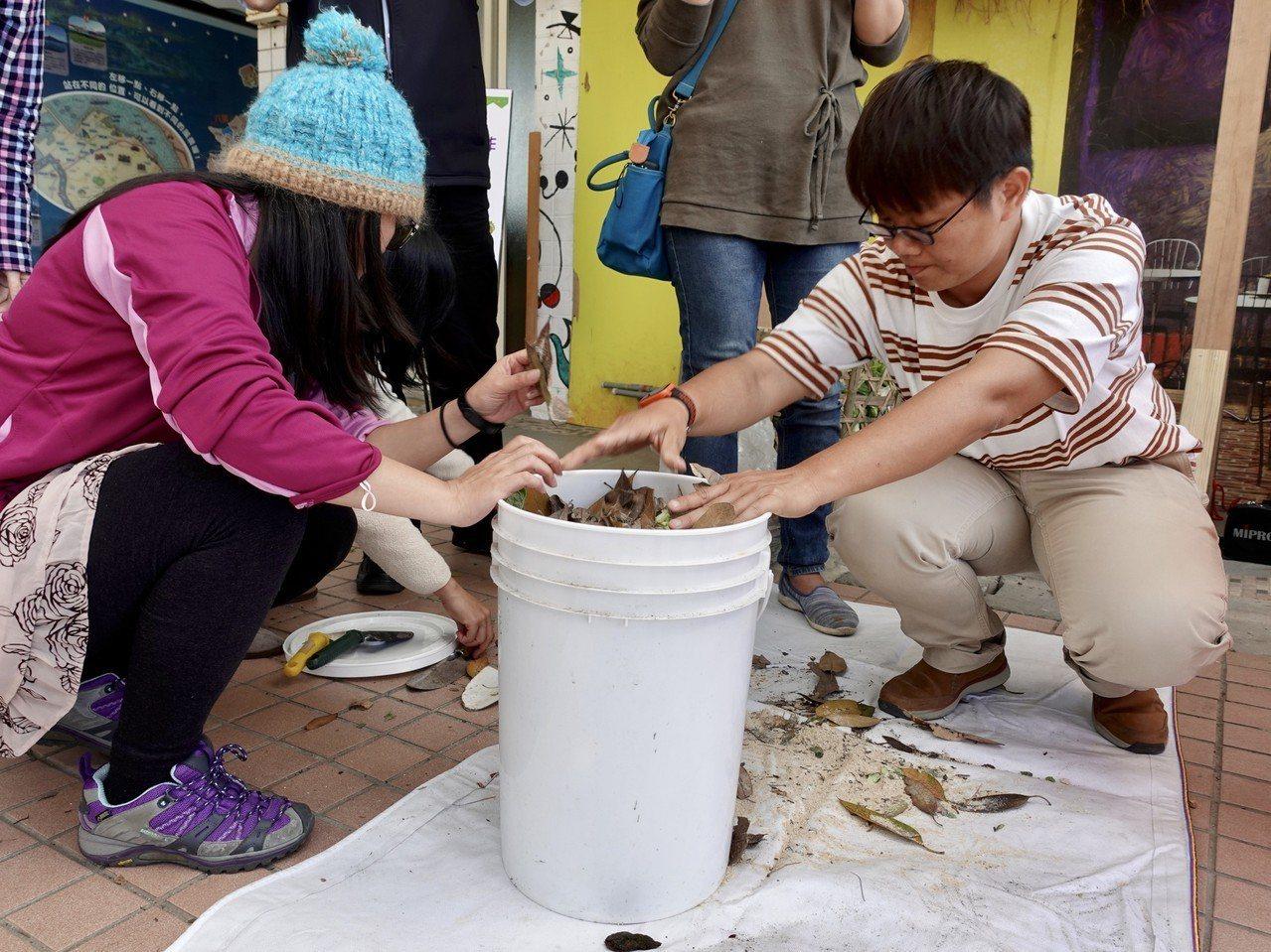 觀摩人員試著自己動手做堆肥。圖/環保局提供
