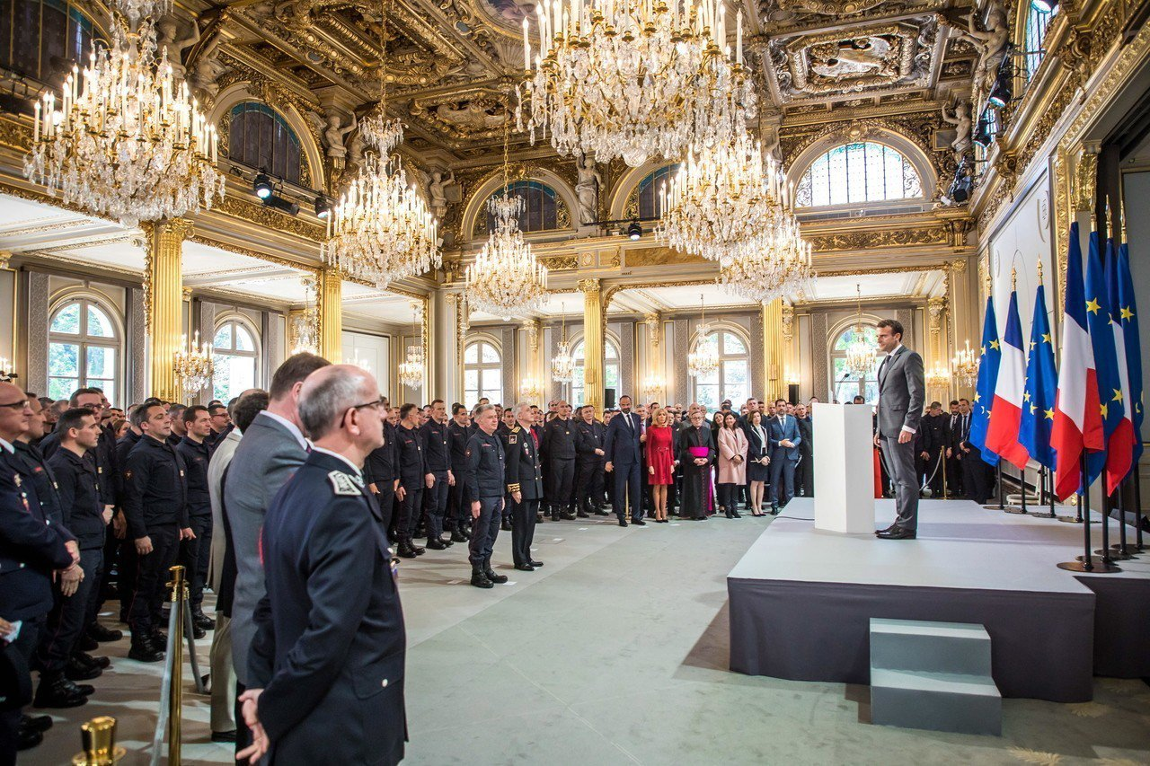 法國總統馬克宏18日在總統府表揚聖母院救火有功的消防員。歐新社