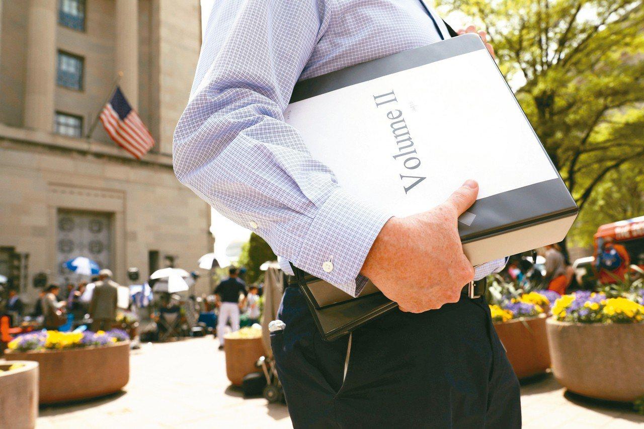 穆勒報告實體書暢銷,圖為記者摟著分成兩冊的報告。 路透