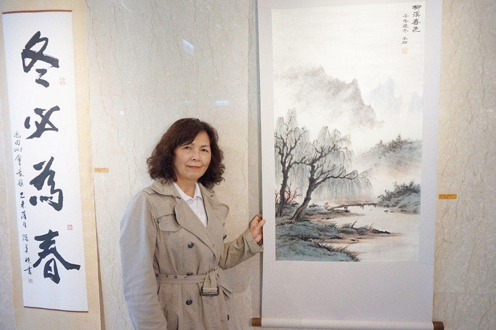 陳美妹與「柳溪春色」山水畫作和「冬必為春」字畫合影。圖/新竹馬偕醫院提供