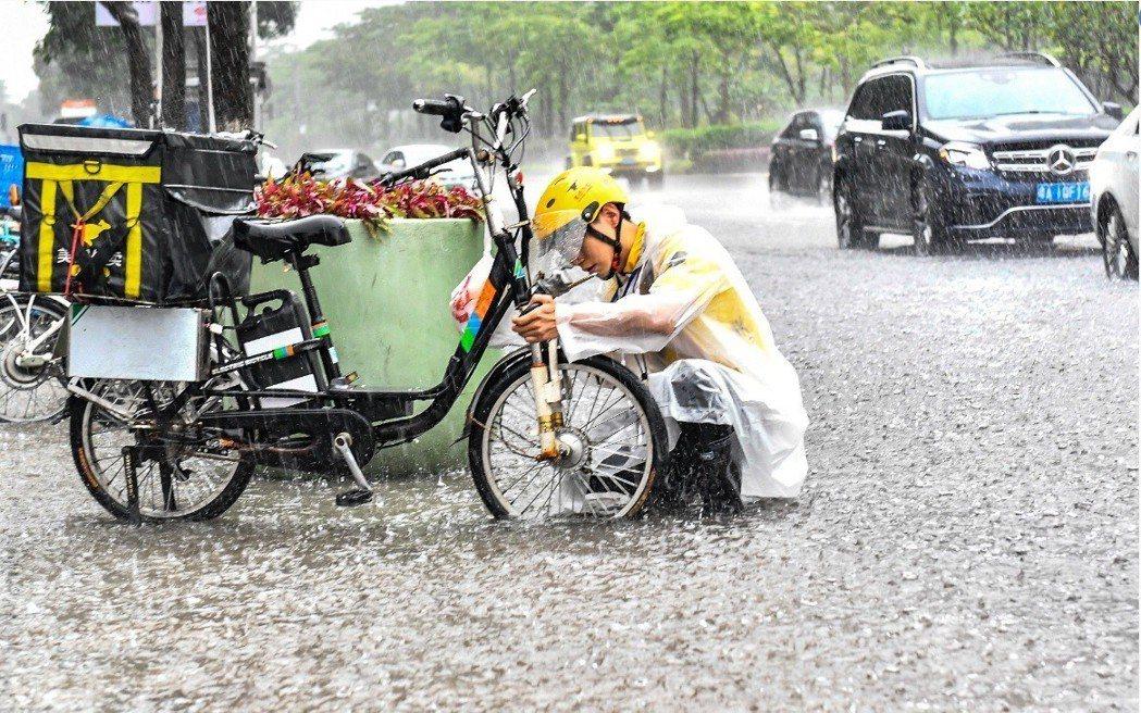 廣東19日遭暴雨冰雹大風夾擊,交通大受影響。圖為一名外送員在雨中修理拋錨的電動車...