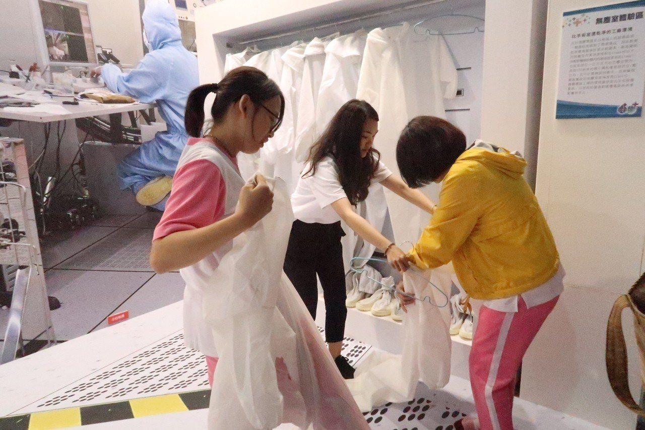 學生在「無塵室體驗區」穿上專業工作服,扮演IC產業幕後功臣的晶片製造工程師。記者...