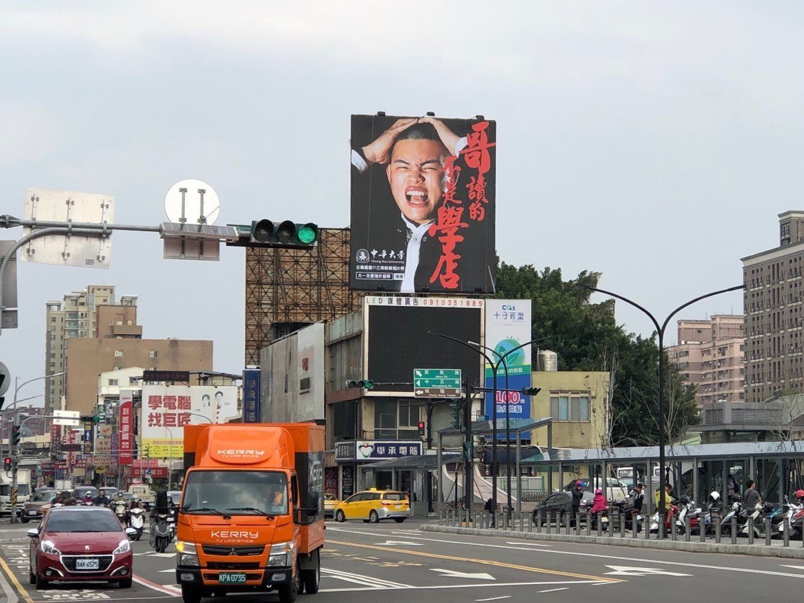新竹火車站前廣場日前豎立起超大看板,上面寫著「哥讀的不是學店」,一旁還有男學生抱...