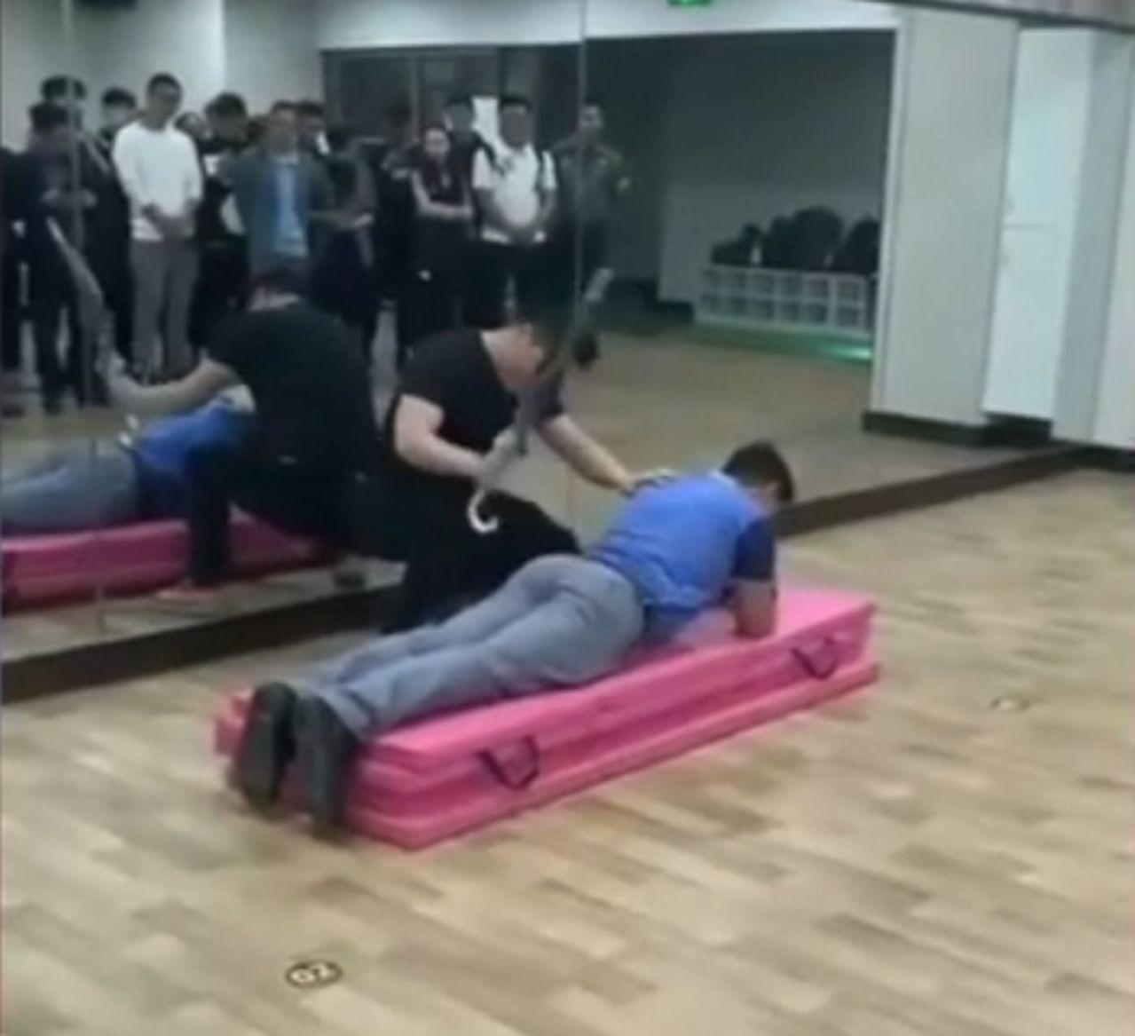健身教練趴在墊子上被打屁股。圖擷自youtube